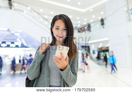 Woman working on smart phone in shopping mall