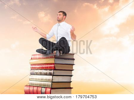 Digital composite of Businessman meditating sitting on Books stacked by sunset with laptop