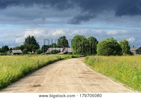 Rural landscape with small russian village on thunderstorm clouds background. Summer evening.