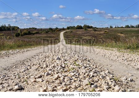 Rural landscape with macadam road through the hills sunny autumn day