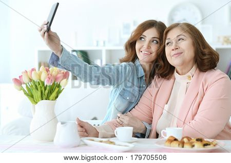 Adult daughter teaches an elderly mother to use a mobile phone