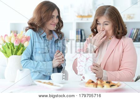 Adult daughter congratulates the elderly mother on the holiday