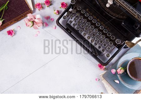 Workspace with vintage typewriter, cup of coffee and books
