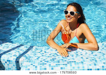 Real female beauty enjoying her summer vacation at swimming pool with alcohol cocktail