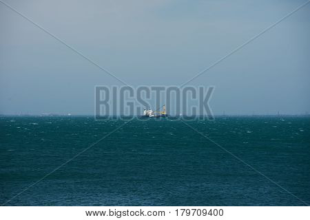 A fishing boat trawler floating in the open waters of the blue Caspian Sea.Concept of spring fishing.