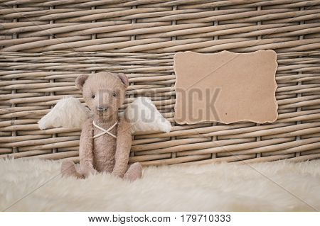 A teddy bear with angel wings sits on the background of a wicker basket. Blank form