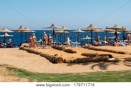 Sharm el-Sheikh, Egypt - February 25, 2013: Elderly tourists on the beach in Sharm el-Sheikh to play bowling on the beach. Seniors on vacation in the resorts of the Red Sea in Egypt in February.