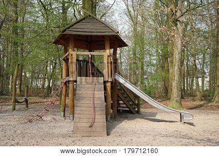 playground in forest with wooden hut, climbing contraption and slide