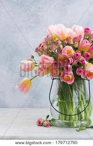 fresh pink and yellow tulips and roses in glass vase close up on gray background