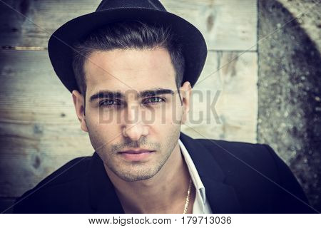 Headshot of handsome young man outdoor in the sun with fedora hat