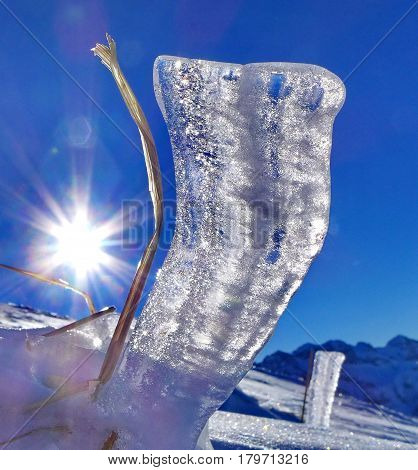 Ray of sun through a prism of ice on a background of the blue sky. Noon. Subpolar Urals, Russia