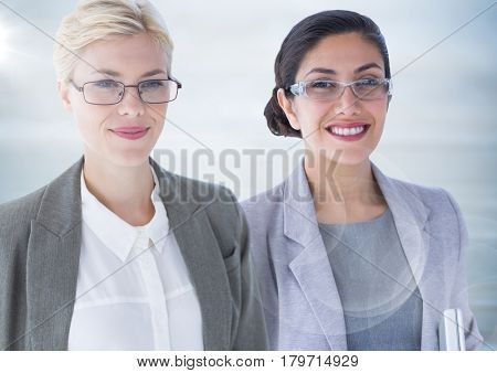 Digital composite of Two business women with flare against blurry grey wood panel