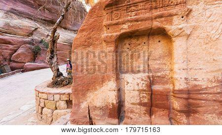 Tourists Near Stone Relief In Al Siq Pass To Petra