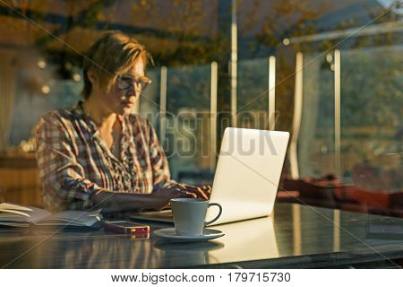 Middle Age Female working on Freelance Project using Portable Computer and making Notes in the Paper Notepad sitting at Table in suburban Cafe throw the Window View focus on Coffee Mug.