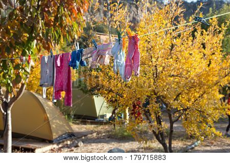 Children Clothing hanging on rope for drying after washing in sunny country garden background