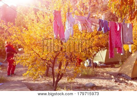 Children Clothing hanging on rope for drying after washing and Mother carrying little Baby on blurred background in sunny country garden