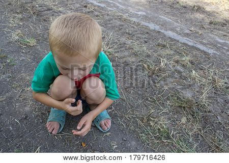 Boy in summer squatted in shorts top view