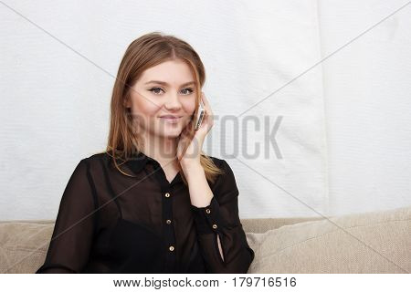 Portrait of young woman talking by phone indoor. Attractive woman talking to someone on her mobile phone and smiling, close up
