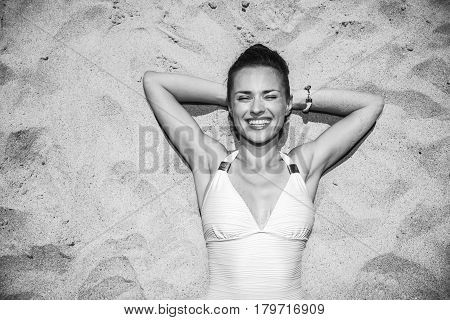 Portrait Of Smiling Woman In Swimsuit Laying On The Sand
