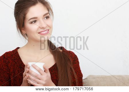 Beautiful girl in red sweater sitting on couch posing and smiling with cup