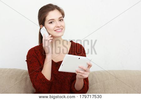 Beautiful girl in a red sweater sits on the couch with a phone and a tablet. He speaks on the mobile. Writes a message