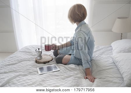 Girl with cup in her hand, kettle and tablet on a white bed lookin through the window, unrecognizable