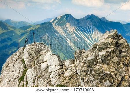 Fixed rope route in the mouintains. Very exposed, great view. Morning or evening light in the mountains. Climbing in the mountains. Alps, Germany, Bavaria.