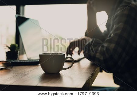 Blur of the man working online at home or part time online jobs with coffee cup on the desk. Add filter dark tone for tired feel or cause to feel in need of rest or sleep. Freelance jobs concept.