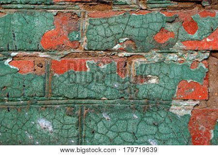 The old green wall with red color and cracks