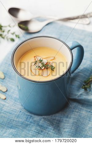 Vegetable cream soup from carrot and potato decorated almonds flakes in blue bowl on rustic background.