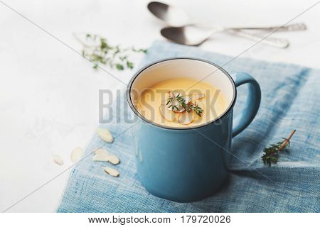 Dietary vegetable cream soup from carrot and potato decorated almonds flakes in blue bowl on rustic background.