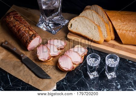 Bottle And Shot Glass With Vodka With Slices Of Smoked Meat On Brown Packing Paper And White Wheat B