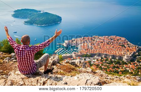 man with opened arms sitting on the edge of a cliff looking down to the Old Town of Dubrovnik Croatia