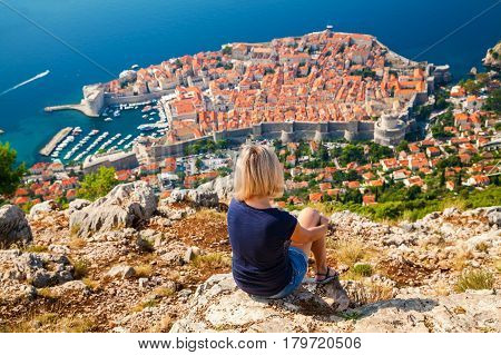 unrecognizable woman looking at the Dubrovnik Old Town sitting on the mountain above the city Croatia