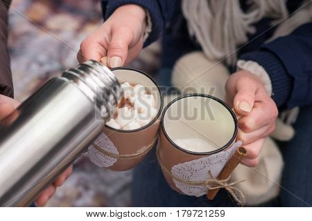 Young couple pours hot drink out of thermos, winter picnic.
