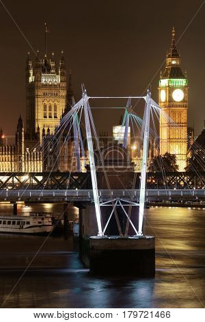 Westminster Palace and bridge over Thames River in London at night