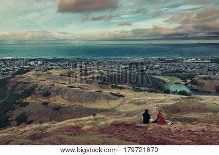 Edinburgh city viewed from top of Arthur's Seat with couple rest in Holyrood Park