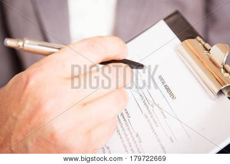 man filling out and signing a rental agreement