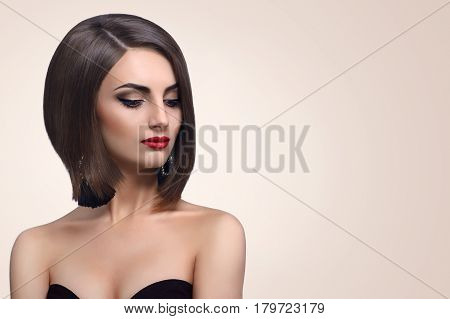 Cropped closeup of a gorgeous elegant female fashion model wearing red lipstick and smoky eyes makeup looking to the camera confidently beauty femininity elegance grace luxury concept.