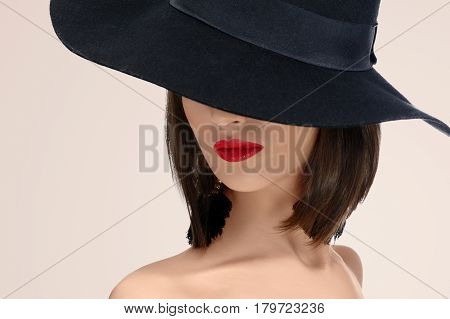 Close up studio portrait of a red lipped woman posing in a hat covering her face mystery mysterious hiding incognito anonymous red lips makeup sexy seductive secret concept .