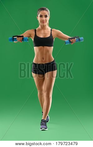 Building stronger body. Vertical full length shot of a gorgeous young sportswoman with strong sexy toned body wearing workout gear showing off her abs lifting weights on green background gym concept