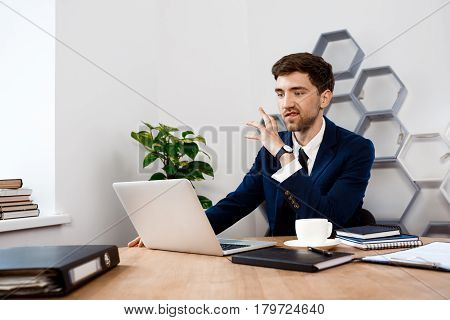 Annoyed young businessman in suit sitting at laptop at workplace, office background.