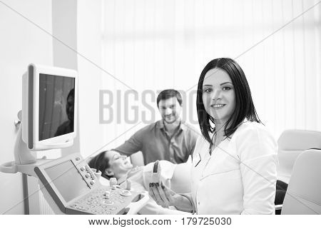 Attractive female doctor smiling to the camera holding ultrasound scanner preparing to check fetal life of her pregnant patient happy loving pregnant couple on the background medical monochrome.