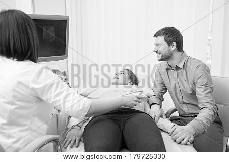 Monochrome shot of a gynecologist checking fetal life of pregnant patient with ultrasonic scanner loving pregnant couple visiting doctor together medical healthcare family pregnancy professionalism