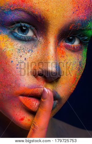 Fashion portrait of beauty model with colorful powder make up show hush sign on dark studio background. Beautiful woman with creative splash makeup. Abstract colourful art make-up, crop
