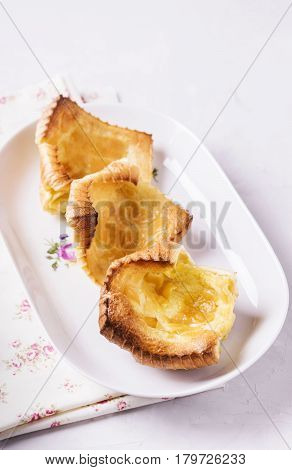 Fresh homemade crunchy popovers on a white plate on a grey concrete background. Selective focus