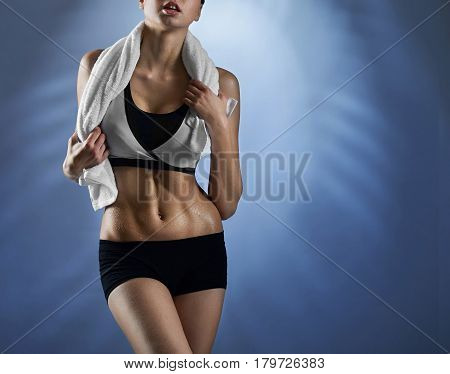On her way to wellness. Cropped closeup of a female fitness model posing with a towel on her neck showing off her toned abs on blue background