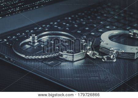 Handcuffs On The Laptop With Blue Digital Code Around. Cyber Hacker Crime Concept.