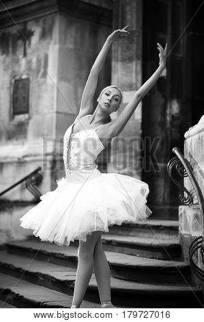 Her perfect lines. Monochrome soft focus shot of a graceful ballerina performing near an old stairway looking to the camera