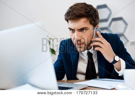 Annoyed young businessman in suit speaking on phone, looking at laptop, sitting at workplace, office background.